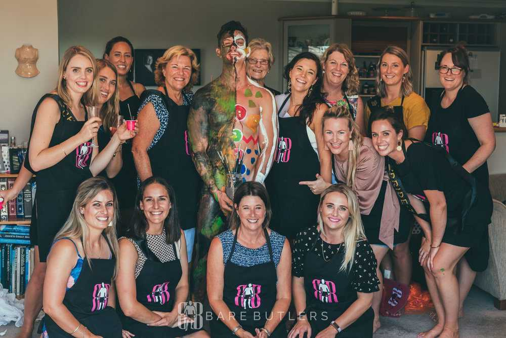 Guests pose with body painting model, covered in paint